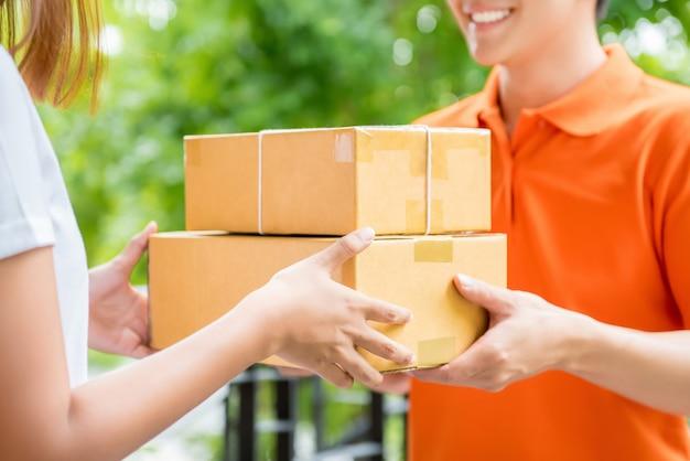 Doręczeniowy mężczyzna dostarcza paczki pudełko klient kobieta