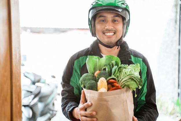 Doręczeniowy mężczyzna dostarcza sklep spożywczego