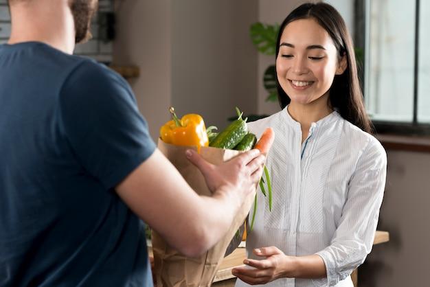 Doręczeniowy mężczyzna dostarcza sklep spożywczy kobieta w domu