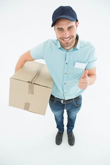 Doręczeniowy mężczyzna gestykuluje aprobaty z kartonem