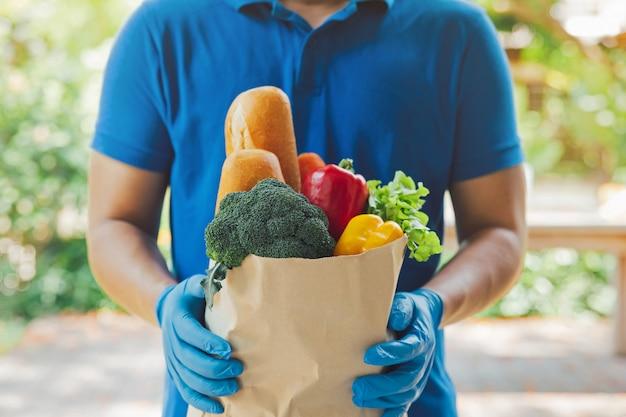 Doręczeniowy mężczyzna jest ubranym higiena rękawiczki w błękita munduru przewożenia pakunku pudełku spożywczy jedzenie od sklepu