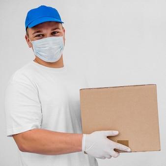 Doręczeniowy mężczyzna jest ubranym maskę i rękawiczki