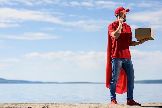 Doręczeniowy mężczyzna jest ubranym superbohatera przylądek outdoors