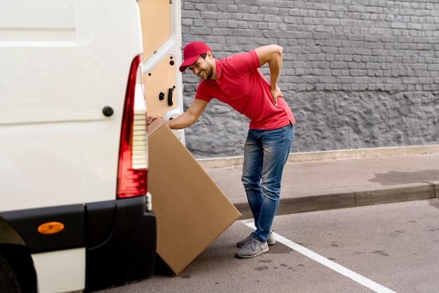 Doręczeniowy mężczyzna ładuje samochód z paczką