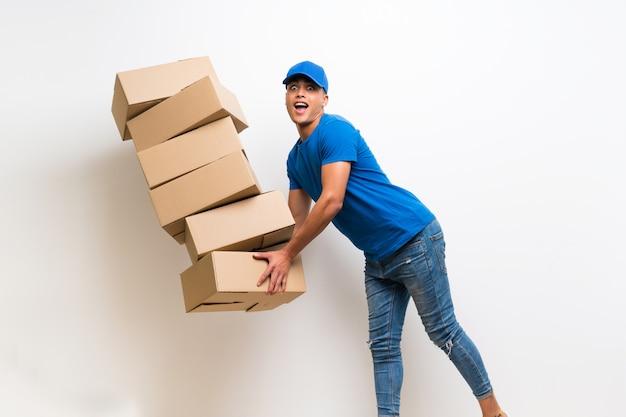 Doręczeniowy mężczyzna nad odosobnioną białą ścianą z partii pudełkami i potknięciem
