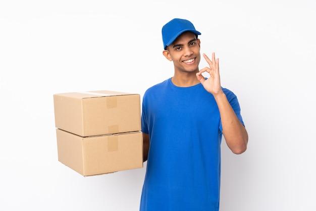 Doręczeniowy mężczyzna nad odosobnioną biel ścianą pokazuje ok znaka z palcami