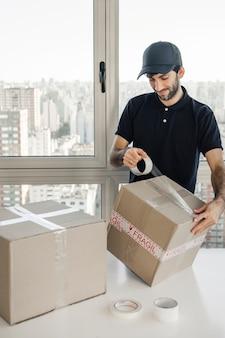 Doręczeniowy mężczyzna pakuje pakuneczek z wiolonczelową taśmą