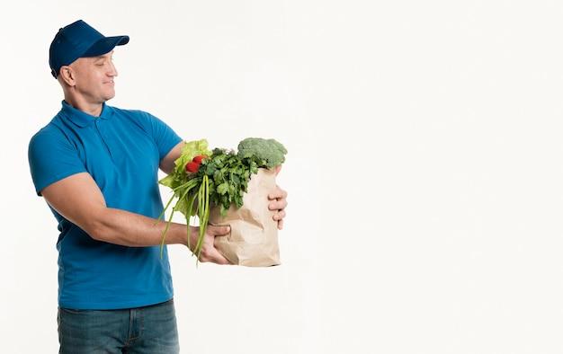 Doręczeniowy mężczyzna patrzeje i sklep spożywczy torba z kopii przestrzenią