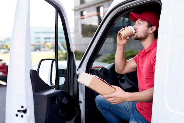 Doręczeniowy mężczyzna pije kawę w samochodzie