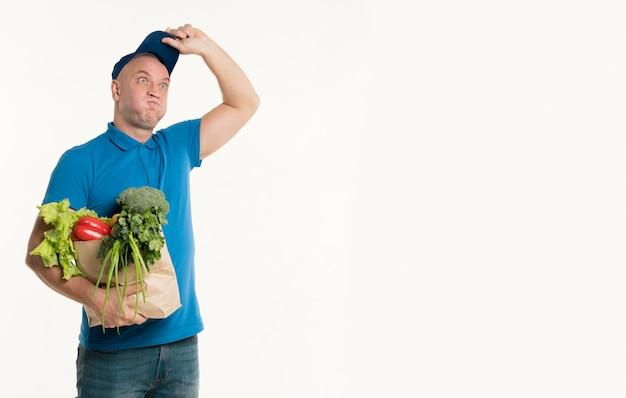 Doręczeniowy mężczyzna pozuje głupio podczas gdy trzymający sklep spożywczy torbę