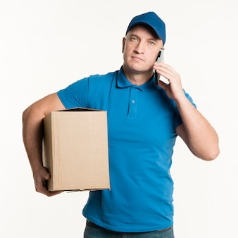 Doręczeniowy mężczyzna pozuje z smartphone i kartonem
