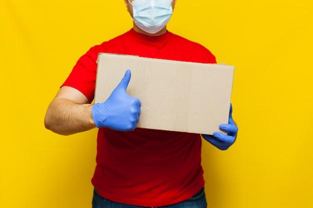 Doręczeniowy mężczyzna trzyma cardbox na kolor żółty ścianie w medycznej masce