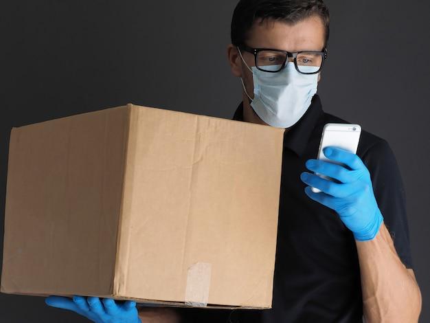Doręczeniowy mężczyzna trzyma kartony i telefon komórkowego w medycznych gumowych rękawiczkach i masce. kopia przestrzeń. zakupy online i dostawa. kwarantanna.