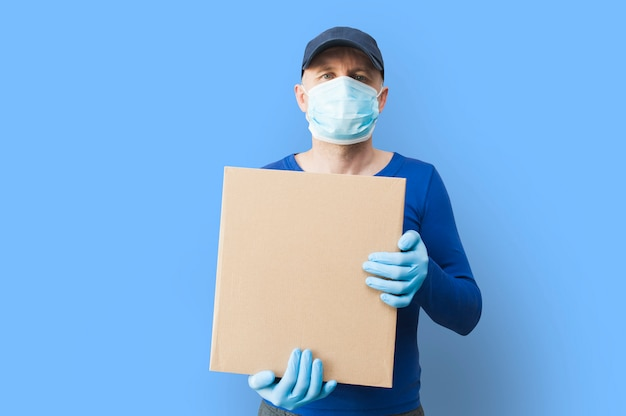 Doręczeniowy mężczyzna trzyma kartony w medycznych gumowych rękawiczkach i masce.