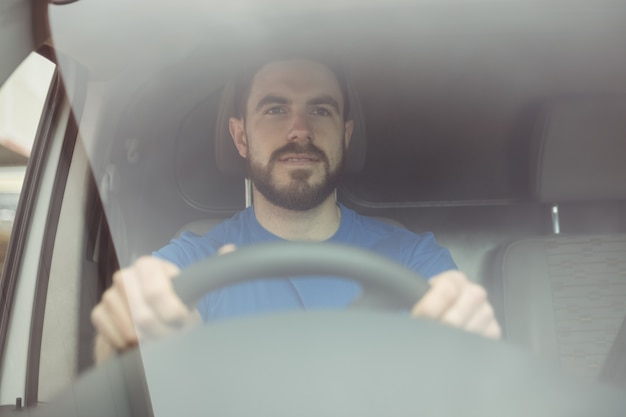 Doręczeniowy mężczyzna trzyma kierownicę jechać jego furgonetką