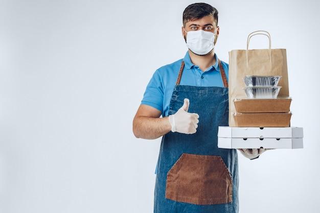 Doręczeniowy mężczyzna trzyma maskę na wynos w masce ochronnej i rękawiczkach medycznych. zgodność z zasadami higieny podczas pandemii covid-19