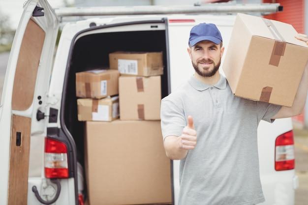 Doręczeniowy mężczyzna trzyma paczkę przed jego furgonetką