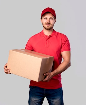 Doręczeniowy mężczyzna trzyma pakunku pudełko