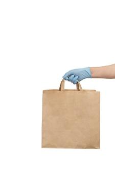 Doręczeniowy mężczyzna trzyma papierową rzemieślniczą torbę z jedzeniem w medycznych rękawiczkach.