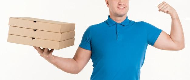 Doręczeniowy mężczyzna trzyma pizz pudełka i pokazuje bicep