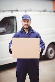 Doręczeniowy mężczyzna trzyma pudełko przed jego furgonetką