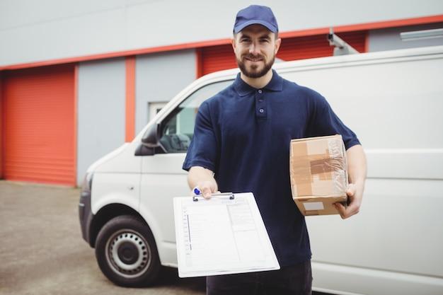 Doręczeniowy mężczyzna trzyma schowek paczkę przed jego furgonetką