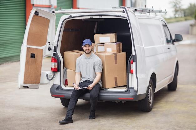 Doręczeniowy mężczyzna trzyma schowek podczas gdy siedzący w przestrzeni ładunkowej jego furgonetki