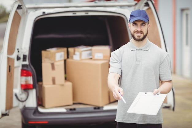 Doręczeniowy mężczyzna trzyma schowek przed jego samochodem dostawczym
