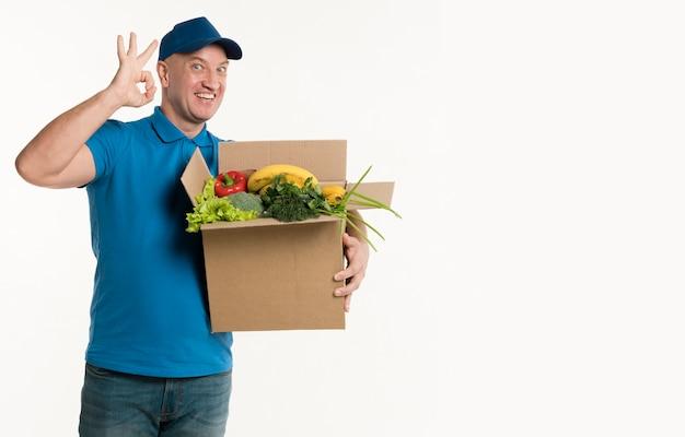 Doręczeniowy mężczyzna trzyma sklep spożywczy pudełko i pokazuje ok znaka