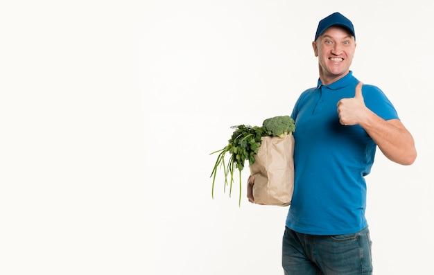 Doręczeniowy mężczyzna trzyma sklep spożywczy torbę i daje aprobatom