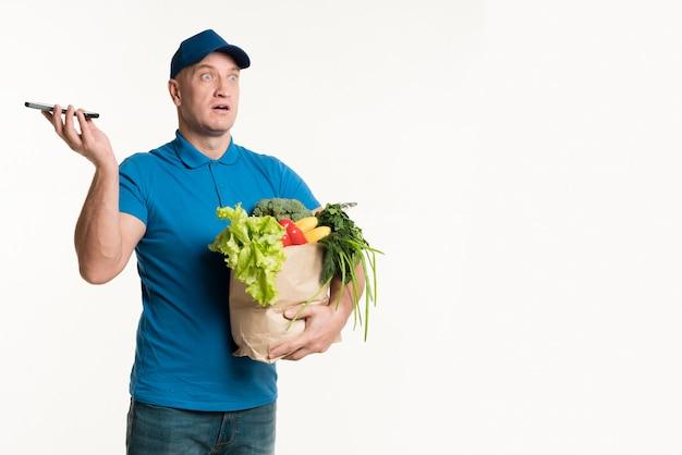 Doręczeniowy mężczyzna trzyma telefon i sklep spożywczy torbę w rękach