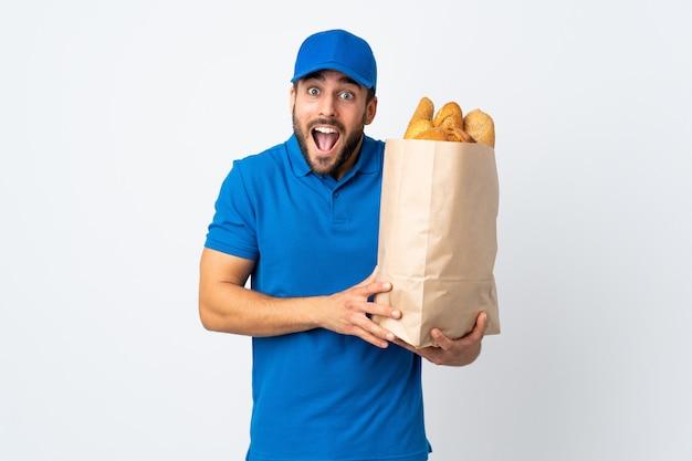 Doręczeniowy mężczyzna trzyma torbę pełno chleby odizolowywający na bielu z niespodzianką i zszokowanym wyrazem twarzy