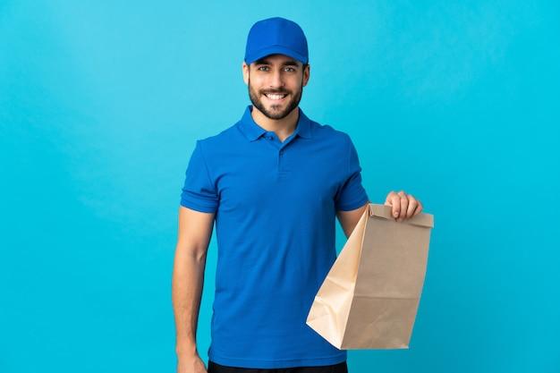 Doręczeniowy mężczyzna uśmiecha się dużo z brodą na błękit ścianie