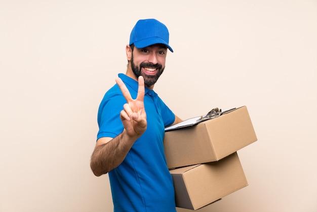 Doręczeniowy mężczyzna uśmiecha się zwycięstwo znaka i pokazuje z brodą nad odosobnioną ścianą