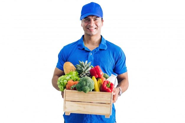 Doręczeniowy mężczyzna w błękita munduru przewożenia pakunku sklepu spożywczego jedzenie z warzywem i owoc na bielu odizolowywającym