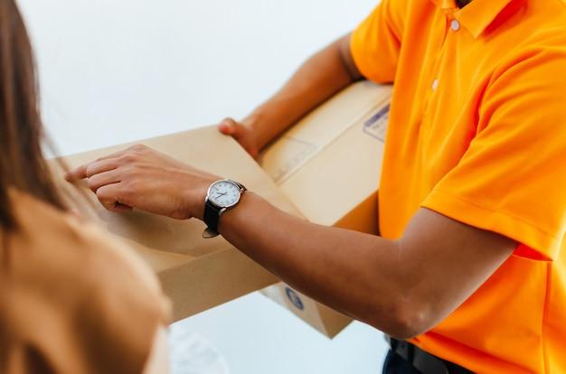 Doręczeniowy mężczyzna w pomarańczowym mundurze z kobietą otrzymującą paczkę pocztową od kuriera w domu, wysyłka ładunków, szybka ekspresowa dostawa, zakupy online, koncepcja logistyczna
