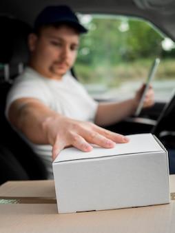 Doręczeniowy mężczyzna w samochodowym macania pudełku