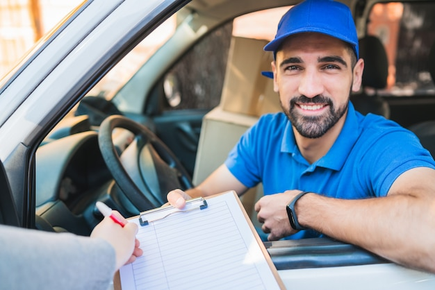 Doręczeniowy mężczyzna w samochodzie dostawczym podczas gdy klient podpisuje wewnątrz schowek