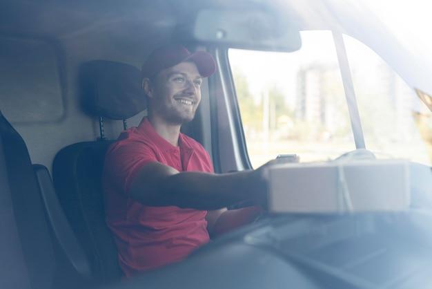 Doręczeniowy mężczyzna w samochodzie z paczką
