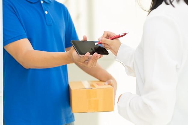 Doręczeniowy mężczyzna wskazuje na smartphone i kobiety odbiorczym pakunku i podpisywać na cyfrowym motłochu