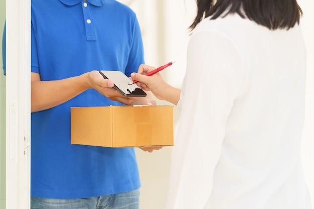 Doręczeniowy mężczyzna wskazuje na smartphone i kobiety odbiorczym pakunku