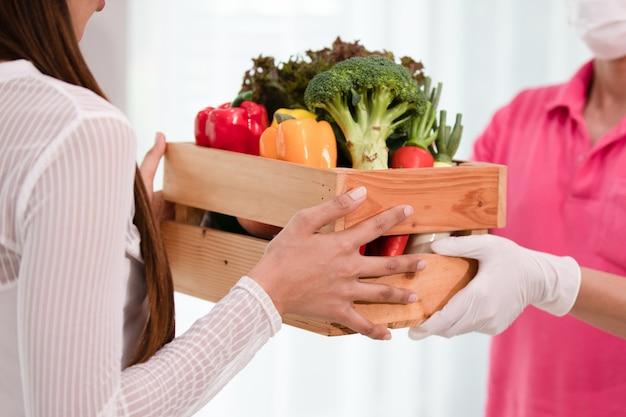 Doręczeniowy mężczyzna wysyła drewnianego pudełko świeże organicznie owoc i warzywo