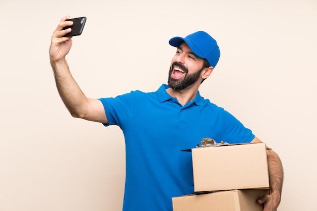 Doręczeniowy mężczyzna z brodą nad odosobnioną ścianą robi selfie