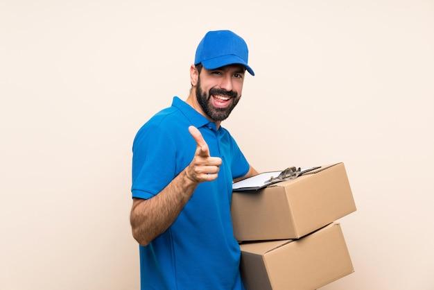 Doręczeniowy mężczyzna z brodą nad odosobnioną ścianą wskazuje przód i ono uśmiecha się