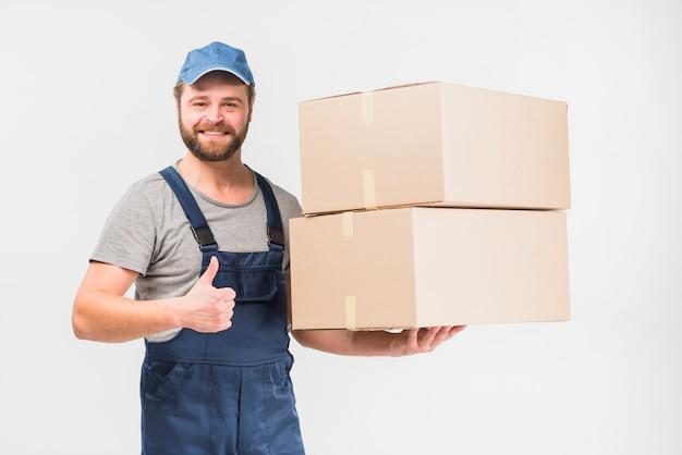 Doręczeniowy mężczyzna z pudełkami pokazuje kciuk up