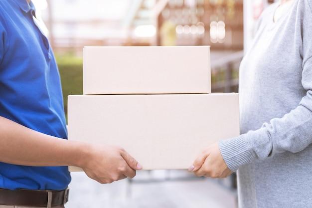 Doręczyciel paczki za pośrednictwem usługi wysyłania do domu. przesyłka ręczna składanie przez klienta przyjmującego dostawę pudełek od dostawcy.