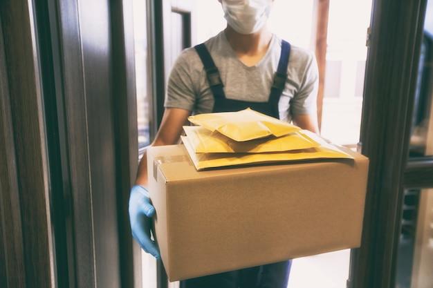 Doręczyciel przekazujący paczki klientowi w swoim domu