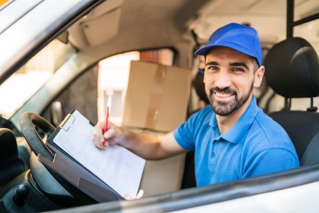Doręczyciel sprawdza listę dostaw w furgonetce.