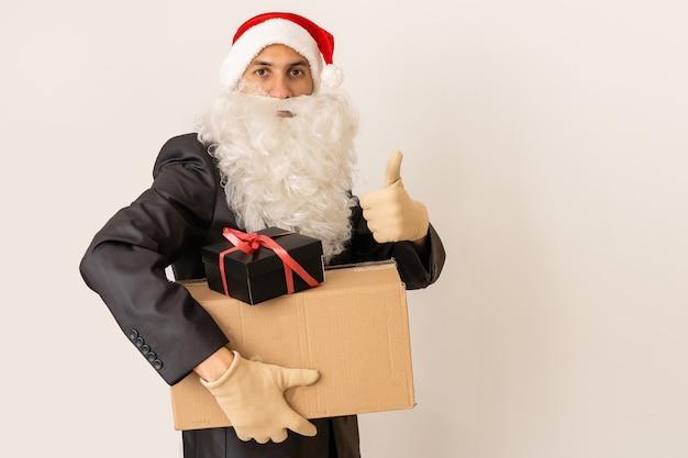 Doręczyciel w czapce mikołaja dostarczający prezent z kokardą - na białym tle