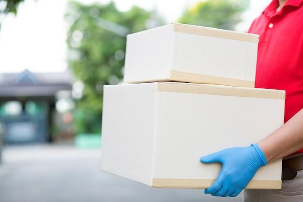 Doręczyciel w czerwonym formularzu wysyła paczki do klientów.